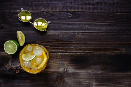Ice drink. Ice tea, lemon, lime and sunglasses on the wooden table, top view. With copy space. Stock Photo