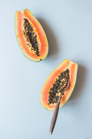 Fresh ripe papaya with spoon on the blue background, top view.