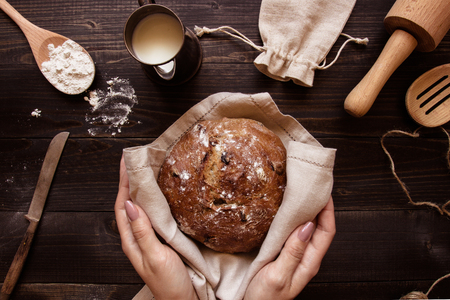 fragrant: Hands holding fresh homemade bread on the dark wooden background top view. Stock Photo