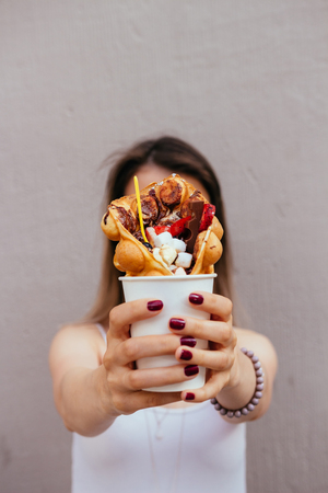Young woman holding bubble waffle with fruits, chocolate and marshmallow, selective focus.
