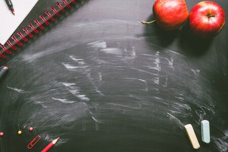 Back to school. School supplies on the chalkboard background with copy space.