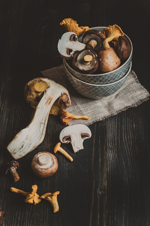 girolle: Fresh mixed forest mushrooms on the wooden black table.