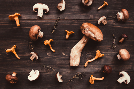 Fresh mixed forest mushrooms on the wooden background, top view.