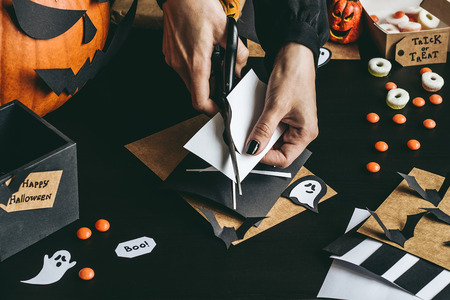 Halloween preparation. Hands making halloween decoration using craft paper.