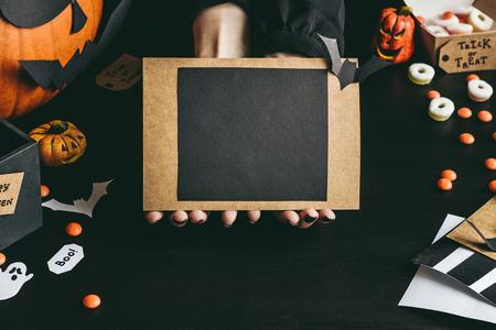 Руки с Хэллоуин карты из бумаги. Копирование пространства. Фото со стока