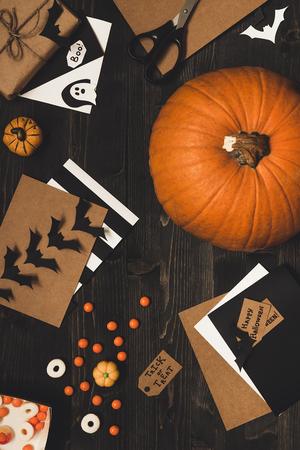 Тыквы на Хэллоуин, конфеты, открытки на Хэллоуин и украшения из бумажной бумаги на деревянном столе.