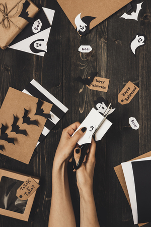 Halloween preparation. Hands making halloween cards and decoration using craft paper. Archivio Fotografico