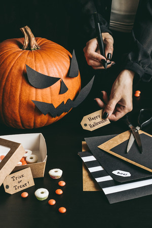 Halloween preparation. Hands making halloween cards using craft paper.