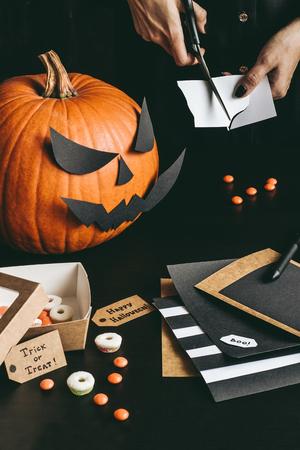 Подготовка к Хэллоуину. Руки, украшающие Хэллоуин с использованием бумажной бумаги. Фото со стока