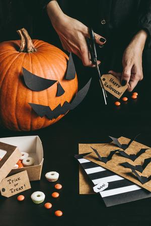 Подготовка к Хэллоуину. Руки, делающие карты Хэллоуина, используя бумажную бумагу.