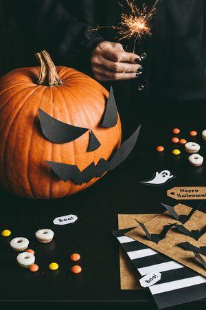 Счастливые приготовления Хэллоуина. Хэллоуинская тыква, сладости, сверкающие и хеллоуин-карты из бумажной бумаги.