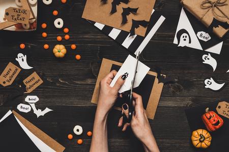 Подготовка к Хэллоуину. Руки, делающие карты Хэллоуина и украшение, используя бумажную бумагу. Фото со стока