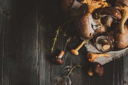 Fresh mixed forest mushrooms on the wooden black table, top view. Copy space Archivio Fotografico