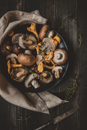 Свежие лесные грибы на деревянном черном столе, вид сверху. Фото со стока