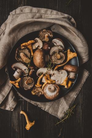 新鮮的森林蘑菇在木製的黑色的桌子,頂視圖上。