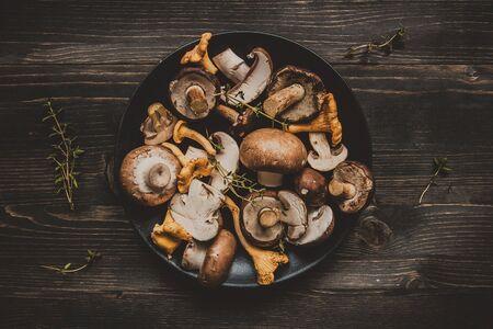 Свежие смешанные лесные грибы на деревянном черном столе, вид сверху.