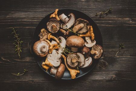 Fresh mixed forest mushrooms on the wooden black table, top view. Фото со стока - 86891244