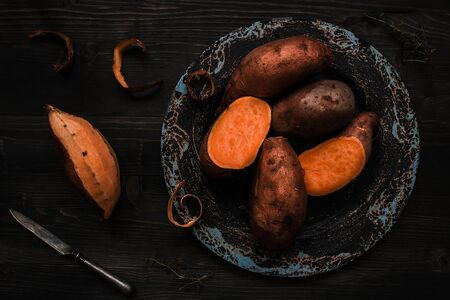 Raw sweet potato on the wooden black table top view.
