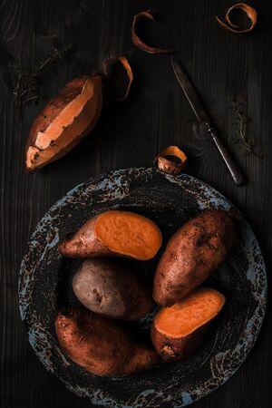 Patate douce crue sur la vue de dessus de table en bois noir.