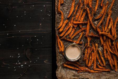 美味的自製紅薯薯條配木製的桌子,頂視圖上的醬。複製空間 版權商用圖片