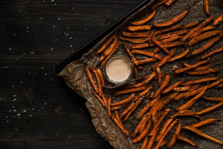 Delicious homemade sweet potato french fries with sauce, top view.