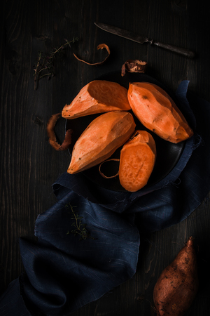 Raw peeled sweet potatoes on the wooden black table top view.