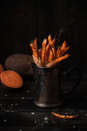 Delicious homemade sweet potato french fries on the wooden table. 스톡 콘텐츠