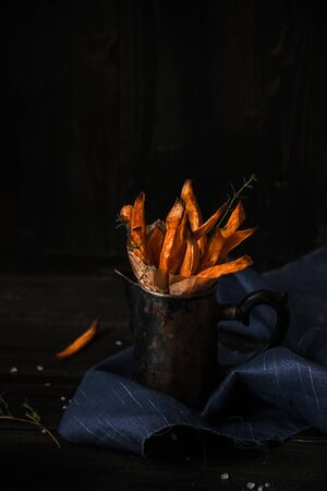 Delicious homemade sweet potato french fries on the wooden table. Archivio Fotografico