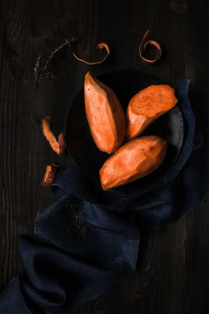 Сырой очищенный сладкий картофель на деревянном черном столе. Фото со стока