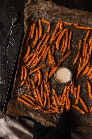Délicieuses frites de patates douces maison avec sauce, vue de dessus.