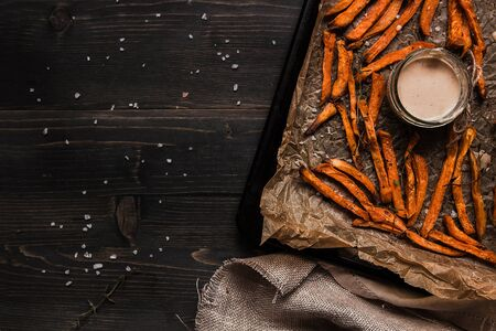 Delicious homemade sweet potato french fries with sauce on the wooden table, top view. Copy space