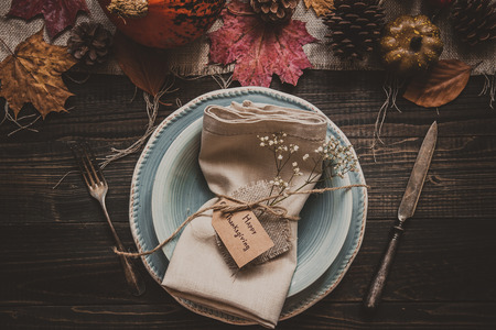 Thanksgiving background. Thanksgiving decoration with cutlery and plate on the wooden table, top view.