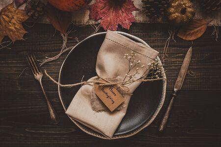 День благодарения. Украшение благодарения с столовыми приборами и табличкой на деревянном столе, вид сверху.