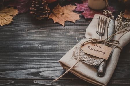 Thanksgiving decoration with cutlery and napkin on the wooden table with copy space. Selective focus. Archivio Fotografico