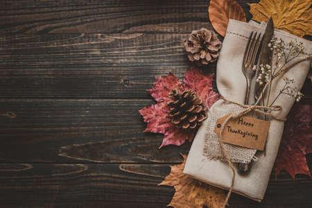 Украшение благодарения с столовыми приборами и салфеткой на деревянном столе, вид сверху. Копирование пространства.