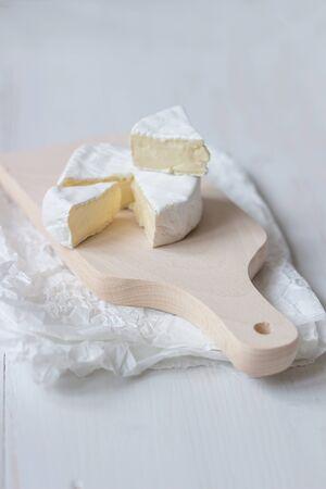 在白色的木桌上切新鮮的卡門培爾奶酪。選擇性的焦點。