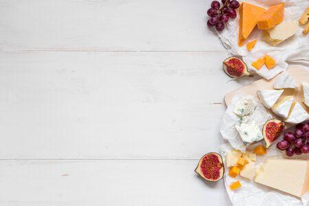 Différents types de fromage avec des fruits sur la table en bois blanche avec espace de copie. Vue de dessus