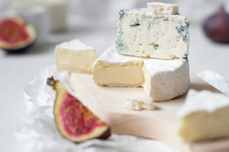 Sliced fresh camembert cheese and blue cheese with figs on the white wooden table. Selective focus. Stock Photo