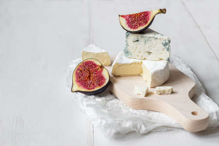 Sliced fresh camembert cheese and blue cheese with figs on the white wooden table with copy space. Selective focus.