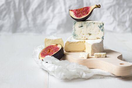 切的新鮮軟制乳酪奶酪和藍紋奶酪與無花果白色木製的桌子上與副本空間。選擇性的焦點。