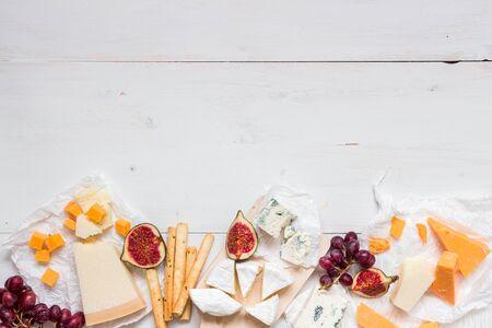 Различные виды сыра с фруктами на деревянном белом столе с копией пространства. Вид сверху. Фото со стока