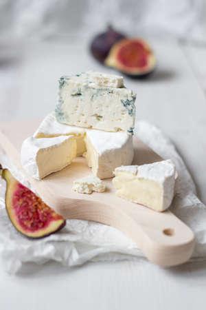 Нарезанный свежий сыр камамбер и голубой сыр с инжиром на белом деревянном столе. Селективный фокус. Фото со стока