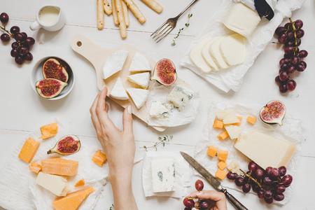 Различные виды сыра с фруктами и закусками на деревянном белом столе. Вид сверху. Фото со стока