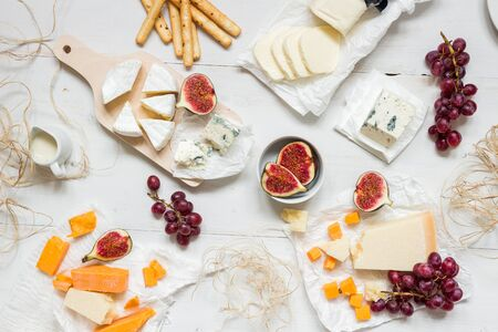 Various types of cheese with fruits and snacks on the wooden white table. Top view.