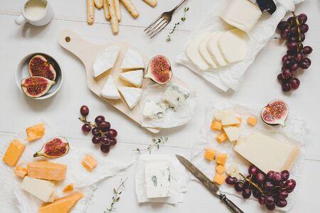 Différents types de fromage avec des fruits et des collations sur la table en bois blanc. Vue de dessus