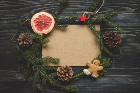 Christmas background. Christmas decoration with fir branches and gingerbread man cookie on the wooden table. Copy space