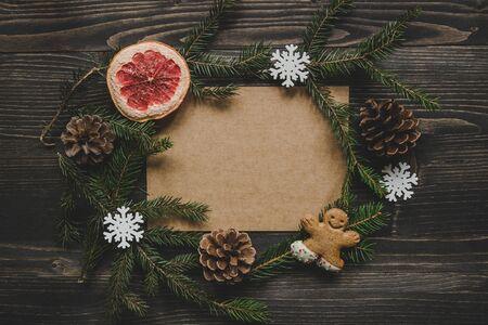Рождественские фон. Новогоднее украшение с еловыми ветвями и пряничным мужским печеньем на деревянном столе. Копирование пространства Фото со стока