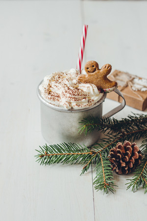 Winter hot drink with gingerbread men cookie and christmas decoration on the wooden white table