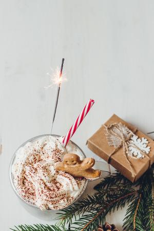 冬季熱飲與姜餅人餅乾,煙火和聖誕裝飾木製的白色桌子上。選擇性的焦點