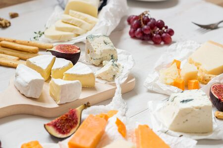 Various types of cheese with fruits on the wooden white table. Selective focus. Stockfoto